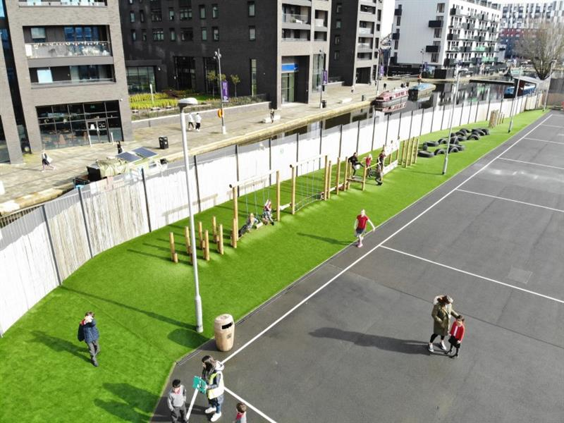 A trim trail with 9 different challenges has been installed onto artificial grass next to the school fencing. There are 5 children playing on the trim trail whilst one child waves to the camera, one child walks to the start of the trim trail and one child stands with a teacher.