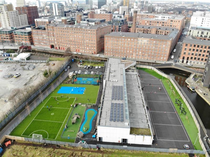 Aerial view of the school playground transformation which includes 2 multi-use games area's, one green and one blue, and a huge trim trail. There are old city buildings behind the school and a canal on the right-hand side of the school.