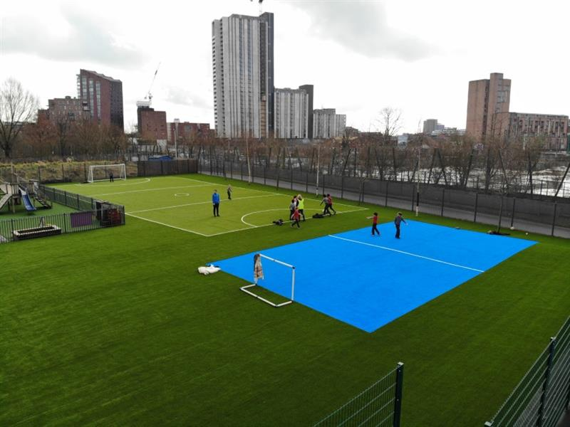 2 multi-use games areas, one is bright blue with 2 children playing on it. The second muga is green with football pitch markings on it with 9 children playing on it and one child is stood in the football next. In the background, there are lots of tall city buildings.