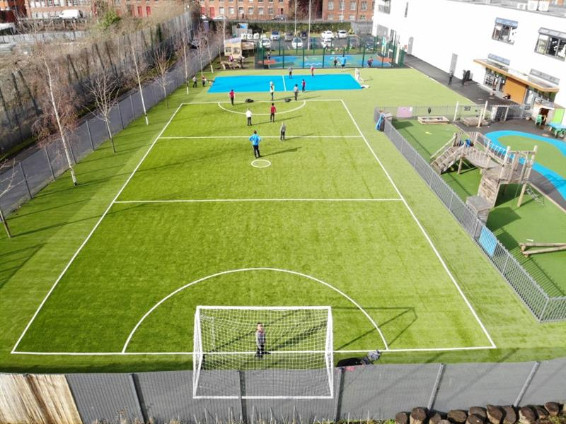 Aerial view of a green multi-use games area with football pitch markings on it. Behind the football pitch is another multi-use games area which is bright blue. These have been installed onto artificial grass next to the white school building.