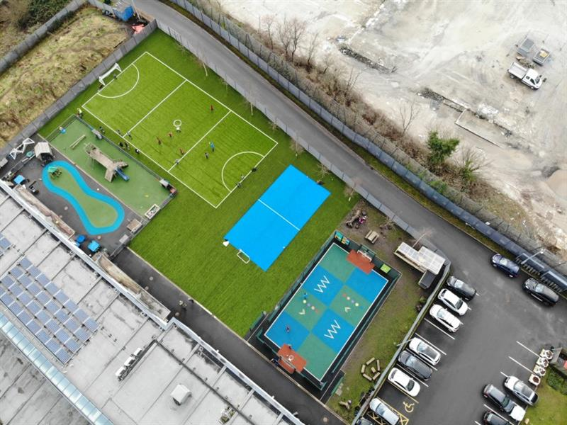 Aerial view of playground transformation which includes 2 new multi-use games areas, one is blue and one is green. The playground is located next to the school car park which has 13 cars parked in it.