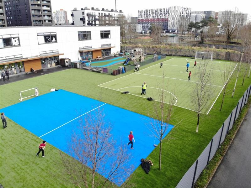 Aerial view of 11 children playing on 2 huge multi-use games area pitches, one of them is bright blue, the other one is green with football pitch markings on it. The pitches have been installed next to the school building.