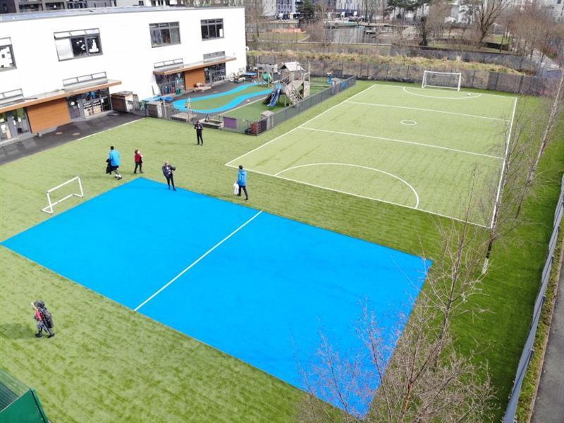 Aerial view of 2 multi-use games areas, one is bright blue and one is green with football pitch markings. There are 6 children walking next to the blue pitch towards the school building. The pitches have been installed next to the school building and a smaller playground.