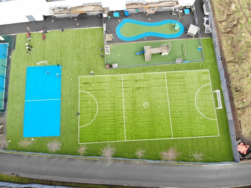 Aerial view of playground transformation which includes 2 new multi-use games areas, one is blue and one is green. There are more than 10 children stood on the artificial grass next to the school building.