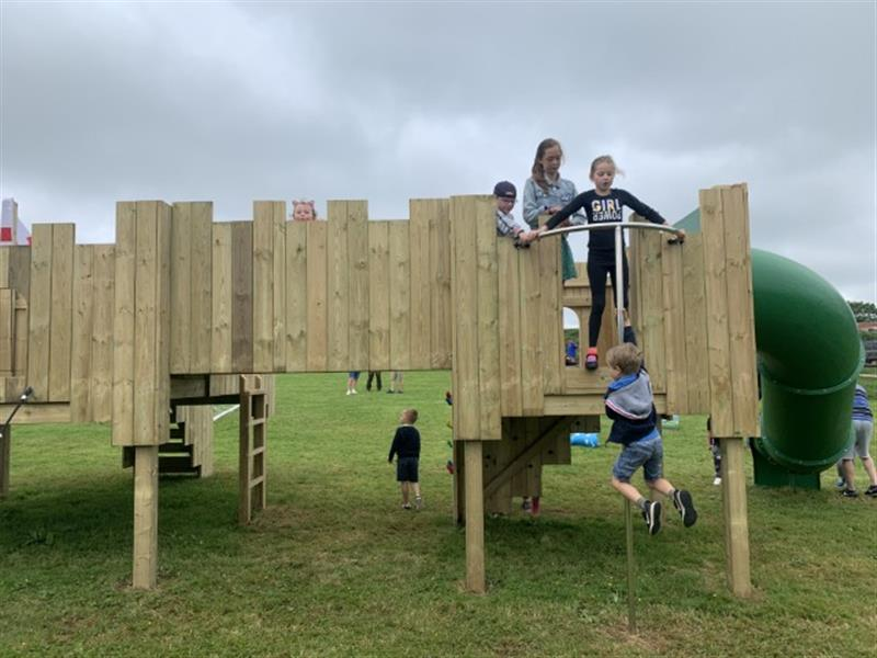 Children lining up on the deck of a play castle waiting to use the firemans pole