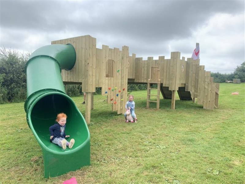 A child racing down the green tube slide of a langley play castle