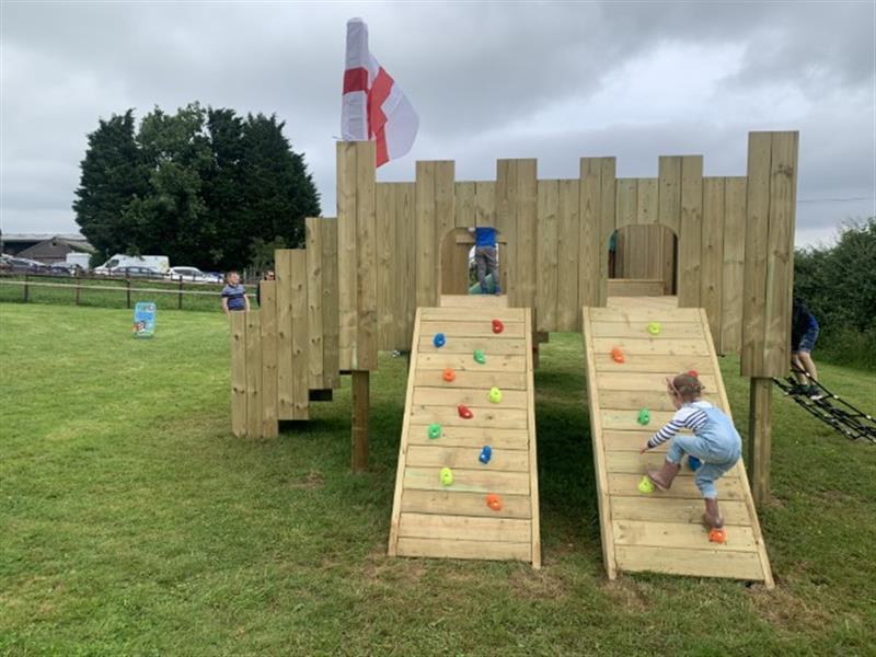 A toddler climbing up the climbing ramp of a langley play castle