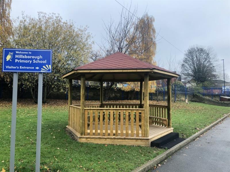 A 5m Gazebo with fenced sides, decked base and internal benches installed onto grass behind a sign that says welcome to hillsborough primary school