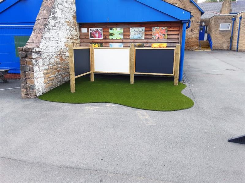 2 chalkboards and 1 whiteboard on posts installed in an L shape against a brick wall with artificial grass underneath