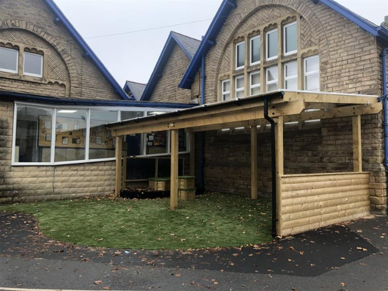 A timber canopy installed against the school building with one side cladded, a performance stage with chalkboard on the opposite side and artificial grass underneath