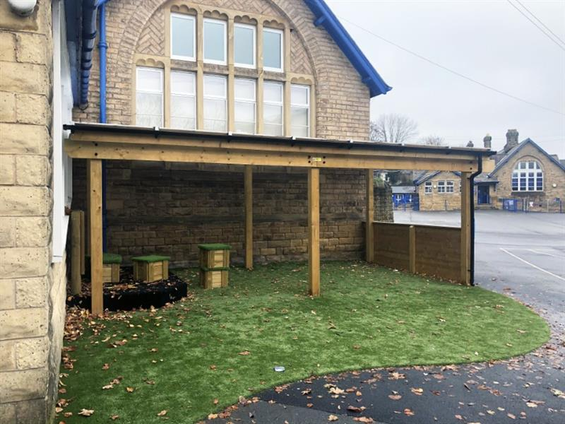 A school timber canopy installed against a building with one clad side on the right, guttering on the roof and artificial grass underneath