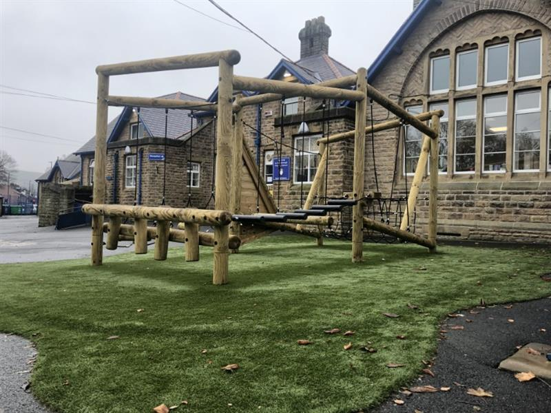 Pentagon play's puzzlewood forest circuit installed on top of artificial grass with a raised section in the middle of the surfacing where shockpad has been installed underneath