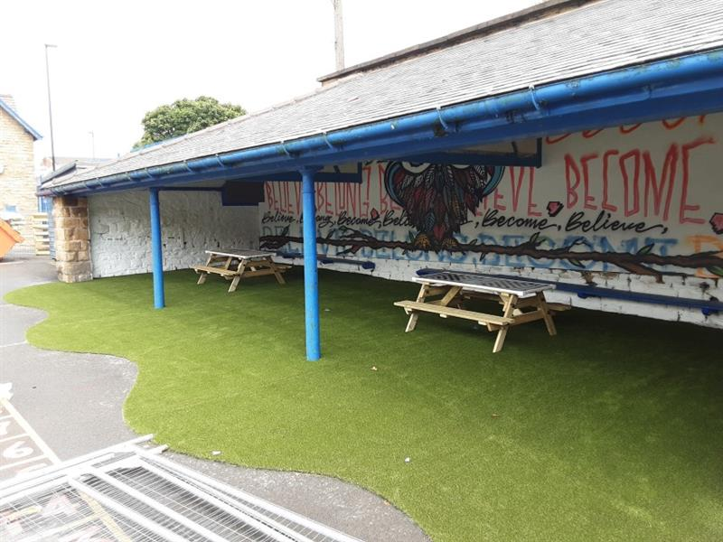 Artificial grass and 2 picnic benches installed under a blue steel canopy with a graffitied brick wall at the rear